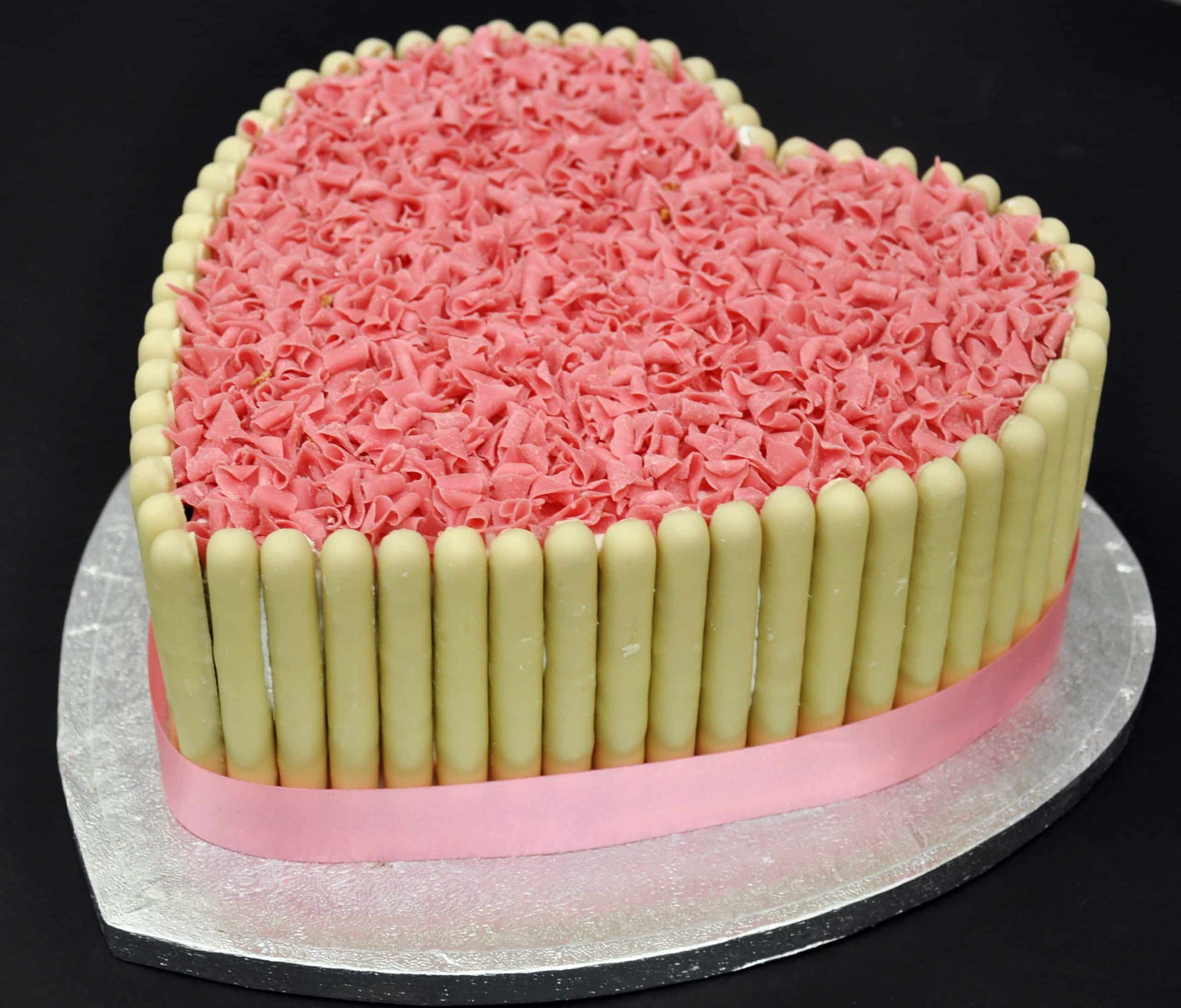 White Chocolate Fingers And Pink Curls Heart Cake